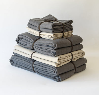 folded stack of 100% linen queen bed-in-a-bag set with duvet pillow shams summer cover flat sheets heavyweight Orkney linen fabric charcoal dark grey natural light brown beige tan colors
