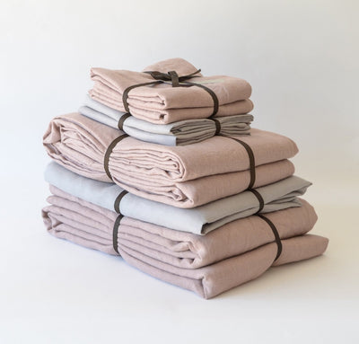 folded stack of 100% linen Cal King bed linen set bed-in-a-bag duvet cover pillow shams bedskirt summer cover sheets light pink rose blush natural beige light brown tan colors