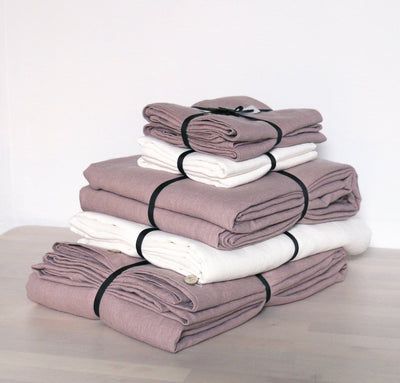folded stack of 100% linen Cal King bed linen set bed-in-a-bag duvet cover pillow shams bedskirt summer cover sheets off-white white natural light pink rose blush colors