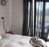 bedroom scene with 100% linen curtains heavyweight Orkney fabric breezy slightly sheer light filtering black color