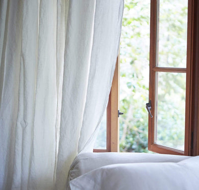 bedroom scene with 100% linen curtains heavyweight Orkney fabric breezy slightly sheer light filtering off-white cream color