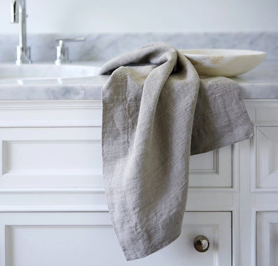 bathroom scene with 100% linen powder room towel set hand towels wash cloths heavyweight Orkney linen fabric antimicrobial fast drying natural light beige brown tan color