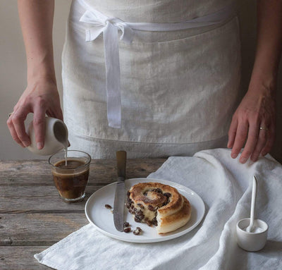white linen bakers chef's style linen apron with pockets. White tea towel and coffee pastry scene