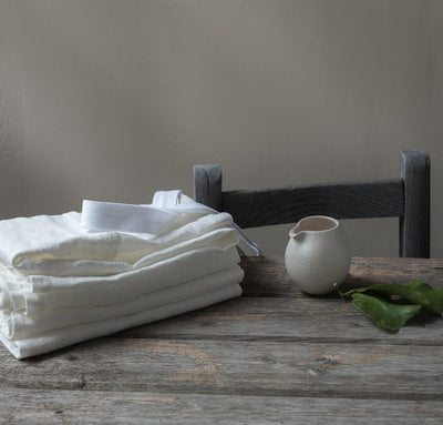 table scene with folded 100% linen tea towels heavyweight Orkney linen fabric off-white color
