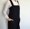 front detail of woman wearing 100% linen pinafore apron wrap design heavyweight Orkney linen fabric with pockets black color