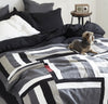 bedroom scene with 100% linen quilt bed blanket cover throw with smooth linen fabric cotton fill patterned design black charcoal dark grey white natural beige red colors