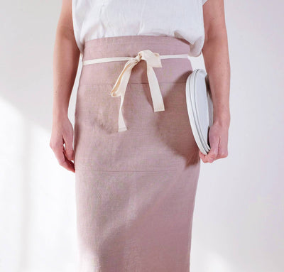 woman wearing 100% linen apron heavyweight Orkney linen fabric rose light pink color