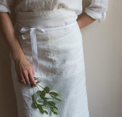 woman wearing 100% linen apron heavyweight Orkney linen fabric off-white white color