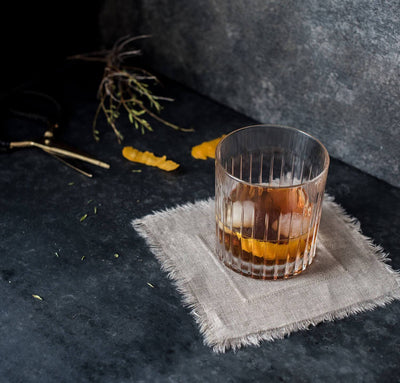 cocktail glass on 100% linen cocktail napkins with frayed raw edge detail natural un-dyed light brown beige color