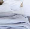 detail of 100% linen bed duvet comforter cover smooth texture lightweight linen fabric pure white color