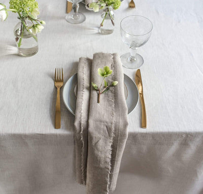 dining table scene with 100% linen napkin smooth texture lightweight linen fabric un-dyed natural beige tan color