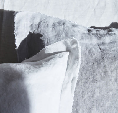 closeup detail of 100% linen pillow slip cover with raw edge detail pure white light grey colors