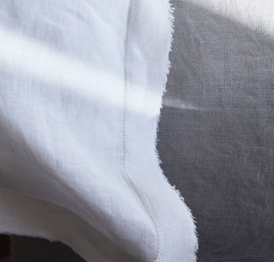 closeup detail of 100% linen pillow slip cover with raw edge detail pure white
