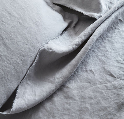closeup detail of 100% linen summer cover blanket with frayed raw edge detail light grey color