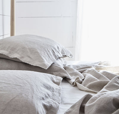 bedroom scene with 100% linen summer cover blanket with frayed raw edge detail natural beige tan color