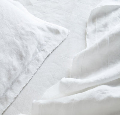 closeup detail of 100% linen summer cover blanket with frayed raw edge detail pure white color