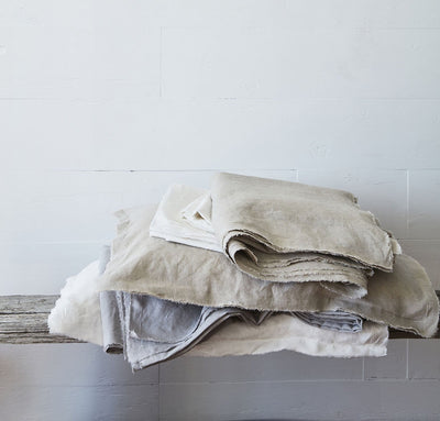 stack of 100% linen raw edge bed set with summer cover blanket pillow cases natural beige tan light grey pure white colors
