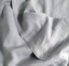 closeup detail of 100% linen summer bed set including bottom sheet pillow cases summer cover blanket light grey color