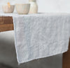closeup detail of table with 100% linen table runner raw edge detail pure white color
