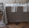 dining table scene with 100% linen tablecloth smooth texture lightweight linen fabric un-dyed natural beige taupe color