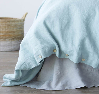 closeup detail of 100% linen bed duvet comforter cover smooth texture mid-weight St. Barts linen fabric twin queen king calking sizes aqua light blue color