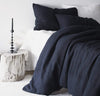 bedroom scene with 100% linen bed-in-a-bag matching bed set including duvet comforter cover two pillow shams smooth texture mid-weight St. Barts linen fabric twin queen king calking sizes ink navy dark blue color