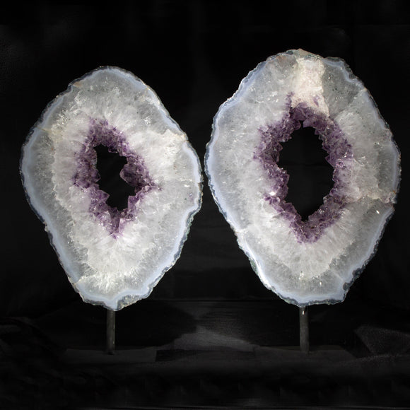 A Pair of Amethyst Sentry Rings  A pair of large, translucent rings cut from a huge Amethyst Geode. Lit from the front of the back they are beautiful, natural centering and grounding addition to any room. Included metal stands present the pieces securely.   8