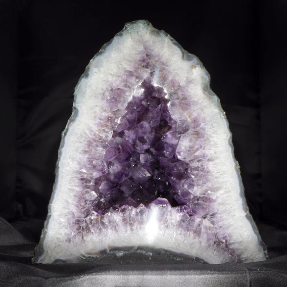 A large, deep purple Amethyst Cathedral Geode. Large, well terminated and richly colored Amethyst crystals line the internal space. This is a 30+ pound, deep and tall display piece that sits exceptionally securely on its wide base.  12