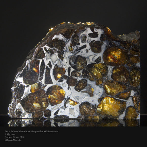 An expertly prepared 9.35 gram part-slice of the Pallasite Meteorite, Imilac featuring external fusion crust, evidence of its descent through the atmosphere and astonishing melt pattern. 4.3 cm x 3 cm, irregular.