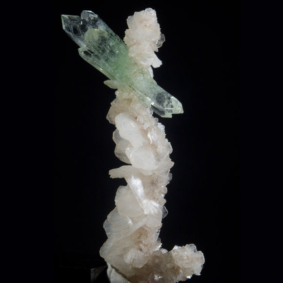 The Fairy - Apophyllite & Stilbite.  One of a kind.  One of the most aesthetic small cabinet pieces you will ever see. Perfect, double terminated Green Apophyllite and a graceful column of Stilbite combine to take your mind on a visual adventure.  It has yet to be determined if this is a Fairy turned to crystal or a crystal becoming a Fairy on a  geologic time scale.  Jalgaon, Maharashtra, India. 12.73 grams, 7 cm, Apophyllite 4 cm.  This macro video exploration will allow it to be shared with the world lon