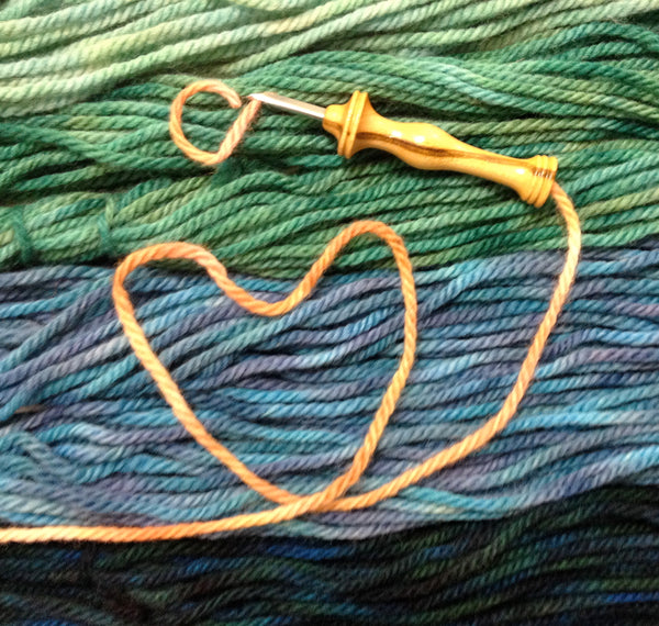 Violet Jane yarn and a heart made from a strand of yarn.
