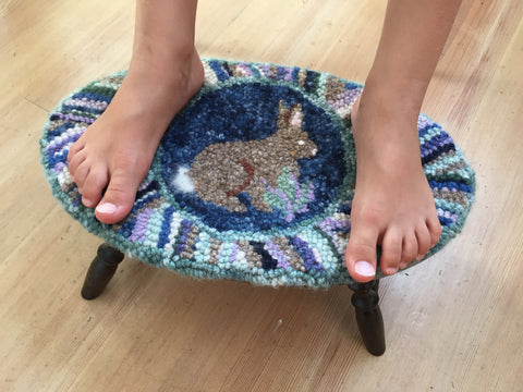 Foot stool with child's feet on top.