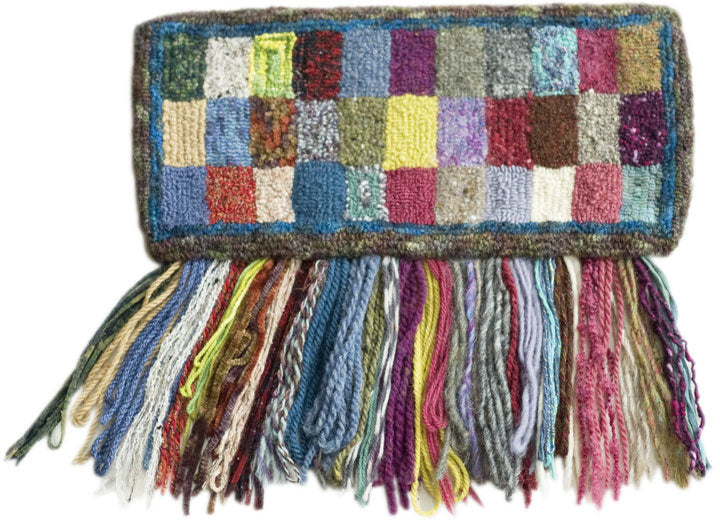 "These are just a few of the many yarns  that work in ""The Mini"" and ""The Mini With Heels.""  The fringe hanging directly below the rectangles  shows what was used to punch the rectangles."