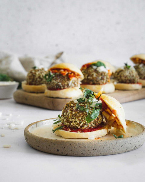 Plant Based Meatball Sliders on a plate and serving tray