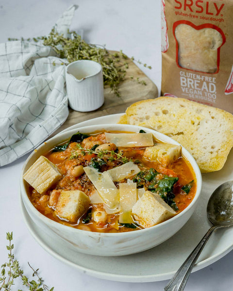 Bowl of gluten-free ribollita soup with a slice of bread srsly gluten-free sourdough