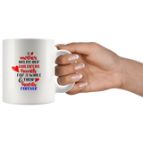 A MOTHER HOLDS HER CHILDRENS HANDS COFFEE MUG