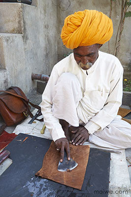 A leatherworker prepares the inside of a bag Jawaja
