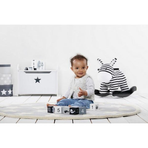 black and white zebra rocker and baby in beautiful monochrome interior
