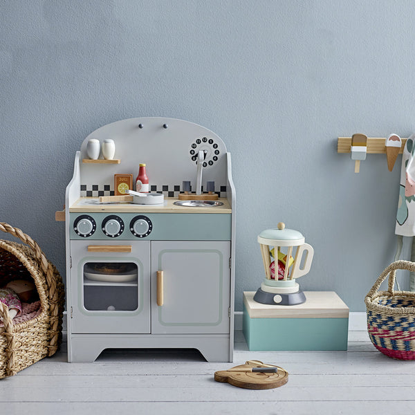 bloomingville mini stove toy in lifestyle photograph with blender, rattan crib and ice cream rack coat stand