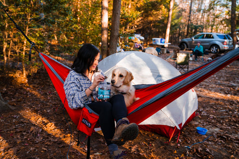 Girl feeding dog treats in hammock