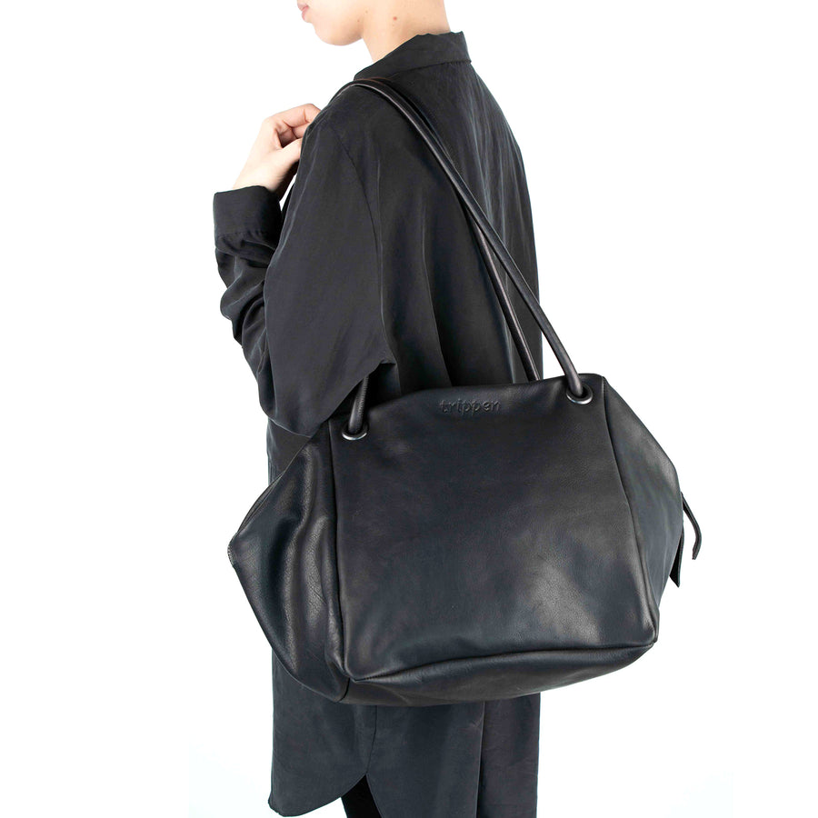 Trippen Alea. Women's handbag in Black leather with long straps. Wrap the straps around your arms and instantly turn your handbag into a square backpack. Made in Germany, Worn on shoulder view.