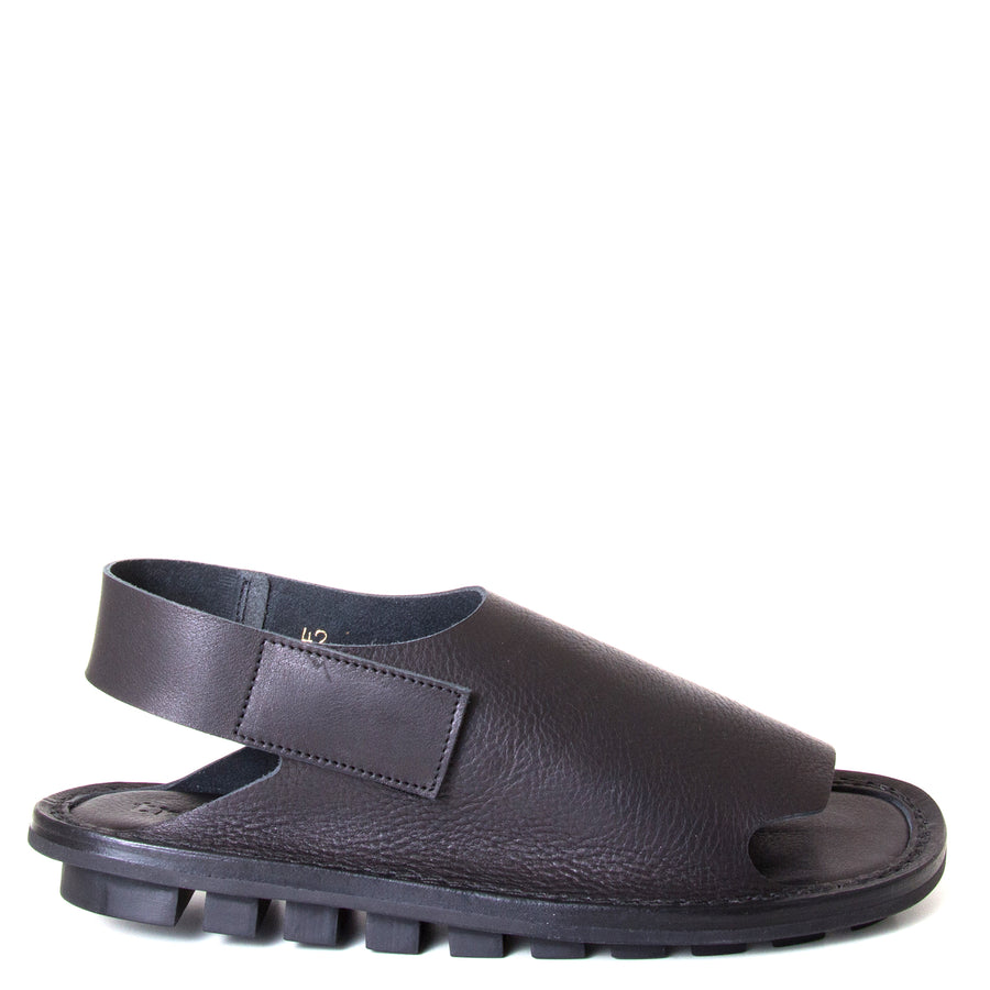 Trippen Clinch. Men's sandal, Soft Black leather upper, velcro strap around heel, flexible rubber sole. Made in Germany. Side view.
