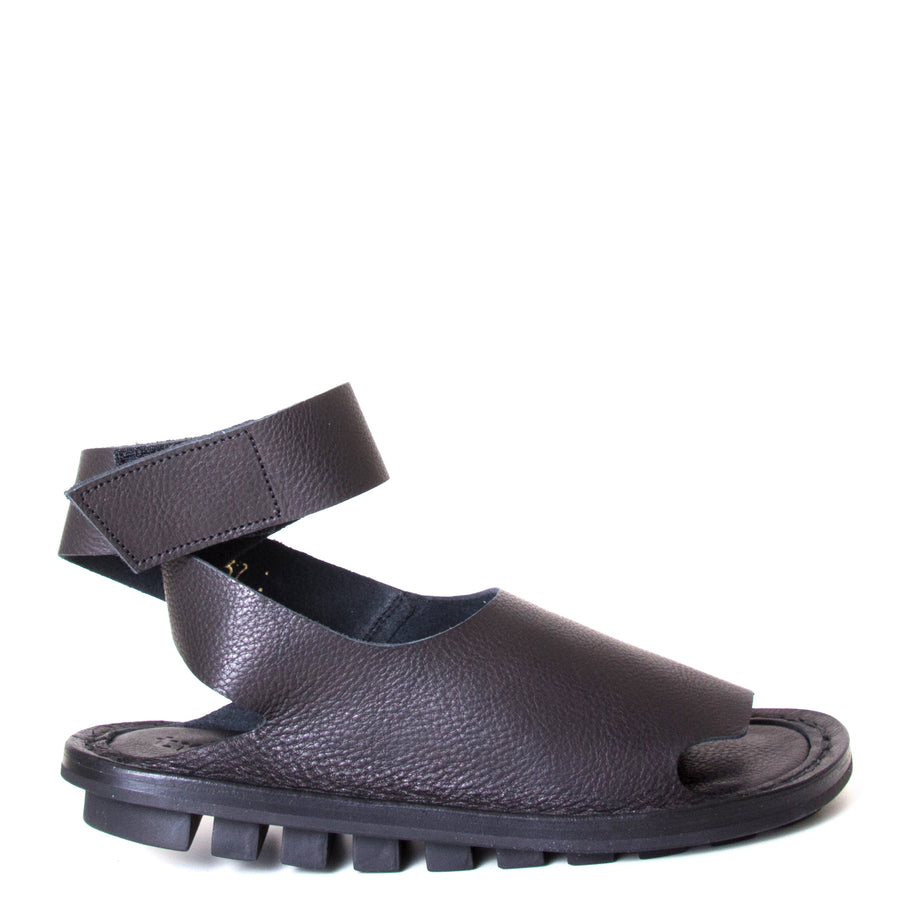 Trippen Hug. Women's sandal in Black leather, rubber sole, ankle strap with velcro for a secure fit. Made in Germany. Side view.