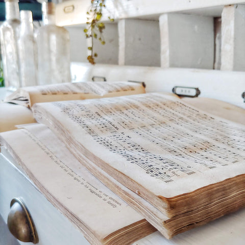 antique hymnal book laid open for display on a white desk