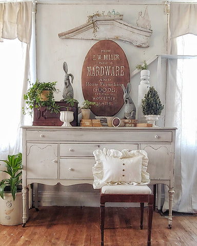antique white buffet decorated for spring with houseplants, vintage books and pillows