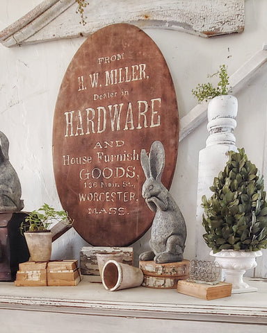 antique hardware store sign with spring greenery vintage books and concrete bunny