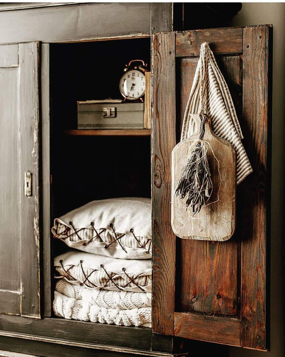 pillows in primitive wood cabinet with antique accents