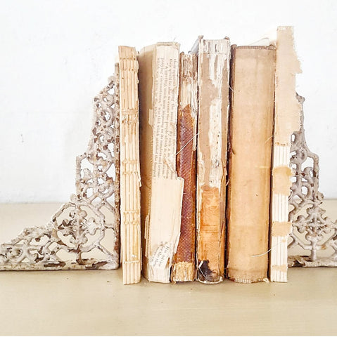 vintage books stacked between chippy white book ends
