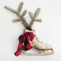 white vintage ice skate with pine branch and red/black buffalo check bow