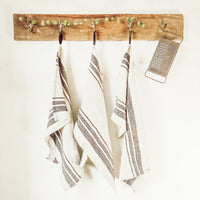 linen tea towels hanging on rustic barn wood with hooks
